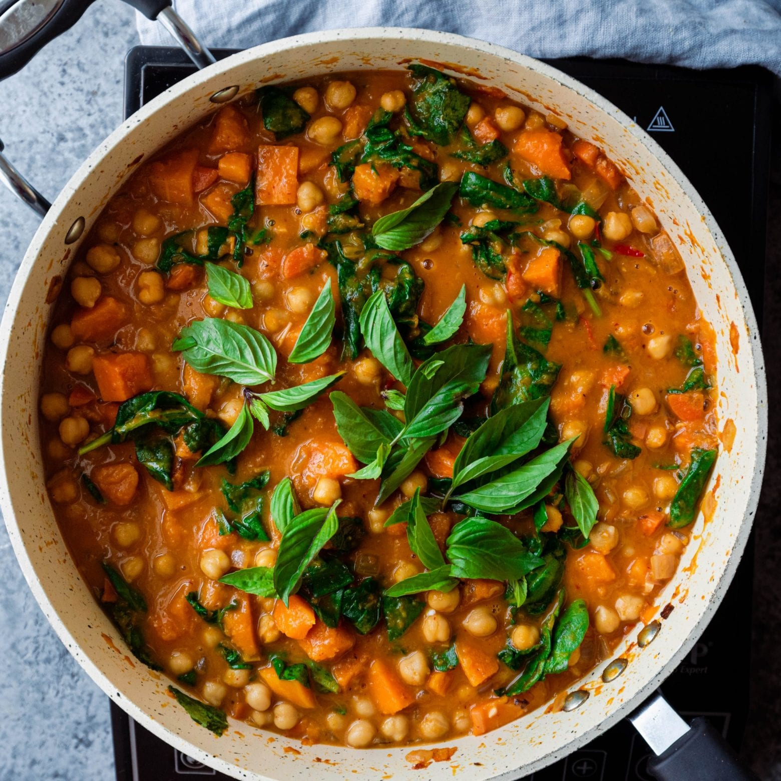 butternut squash curry with chickpeas and thai basil in frying pan