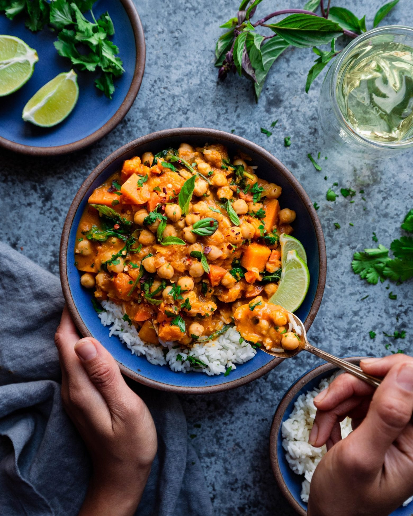 hands spooning Thai butternut squash curry with rice
