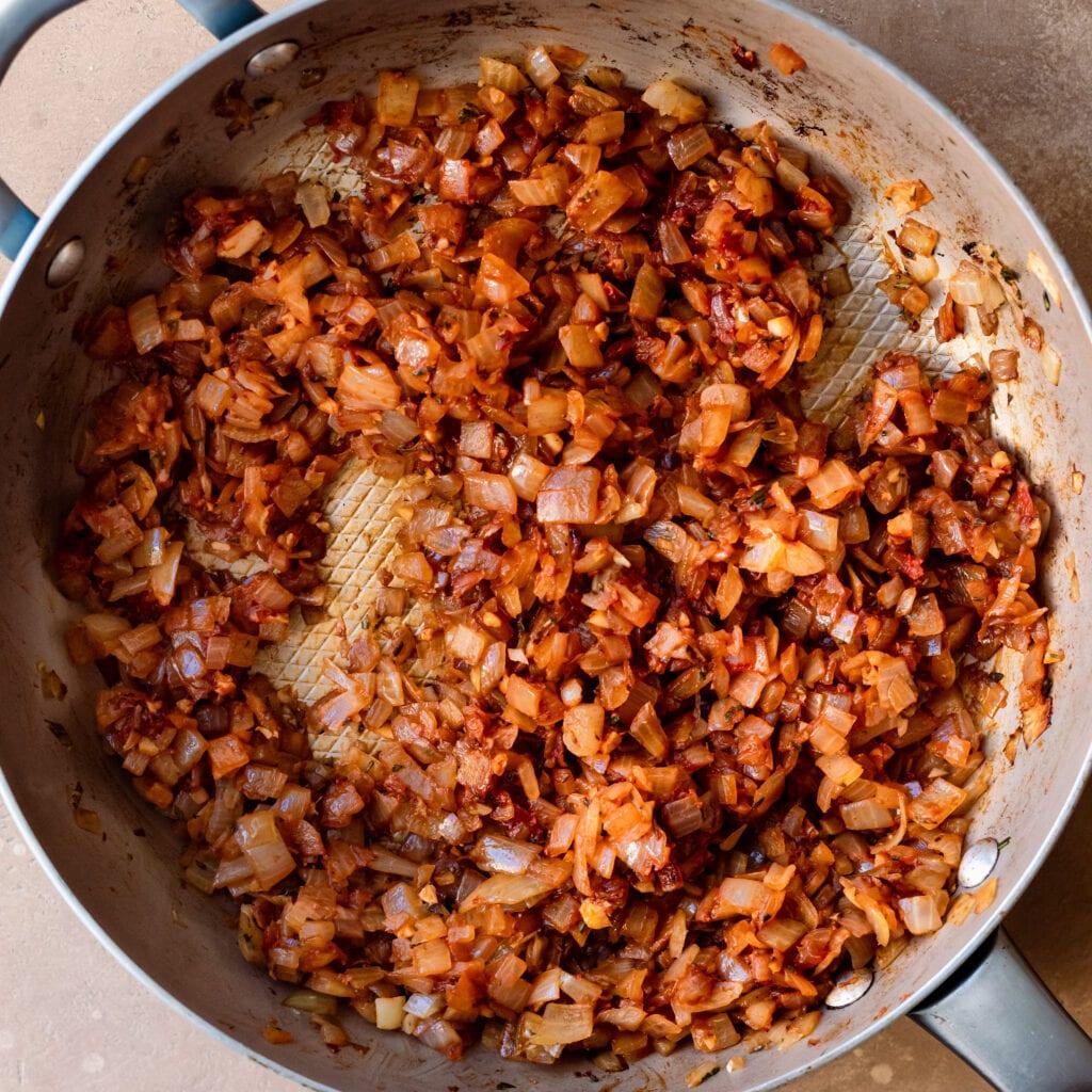 adding tomato paste to onion garlic and herbs mixture