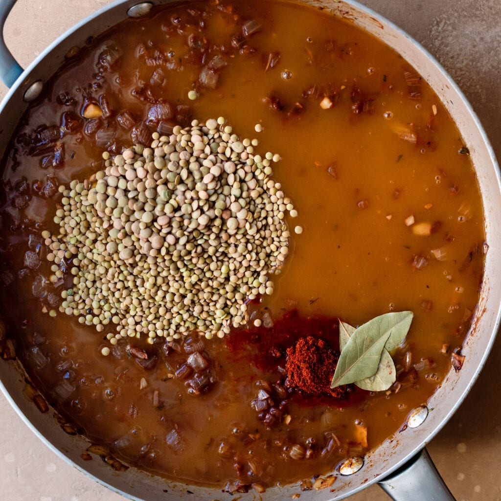 adding vegetable broth, lentils, bay leaves and paprika to saute pan