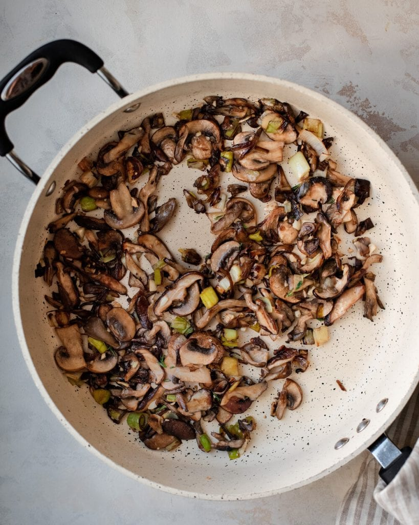 mushrooms and leeks sautéing in pan