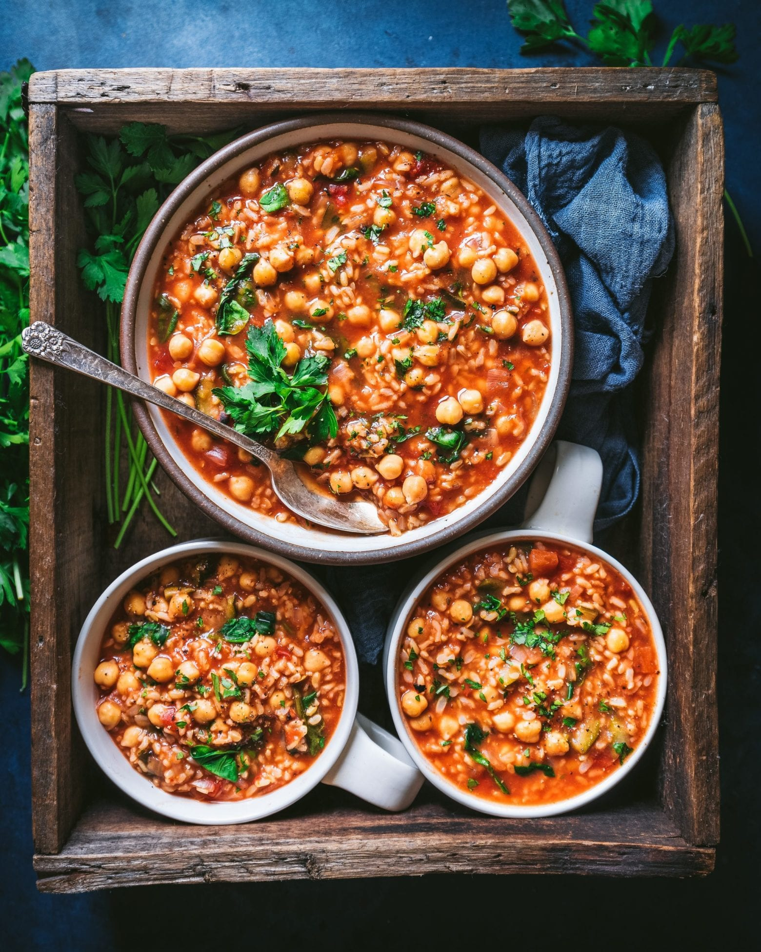 chickpea tomato brown rice stew in one large pot and two smaller soup bowls