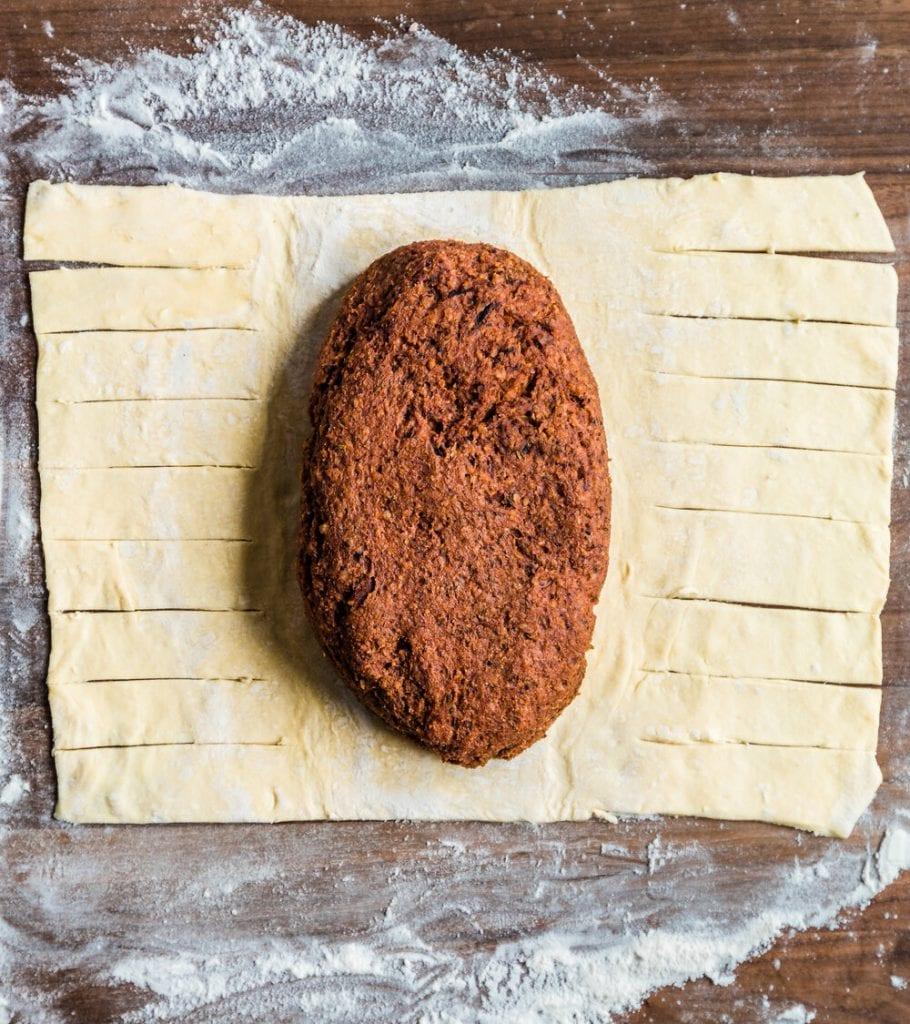 vegan mushroom wellington sitting on unbaked sliced pastry