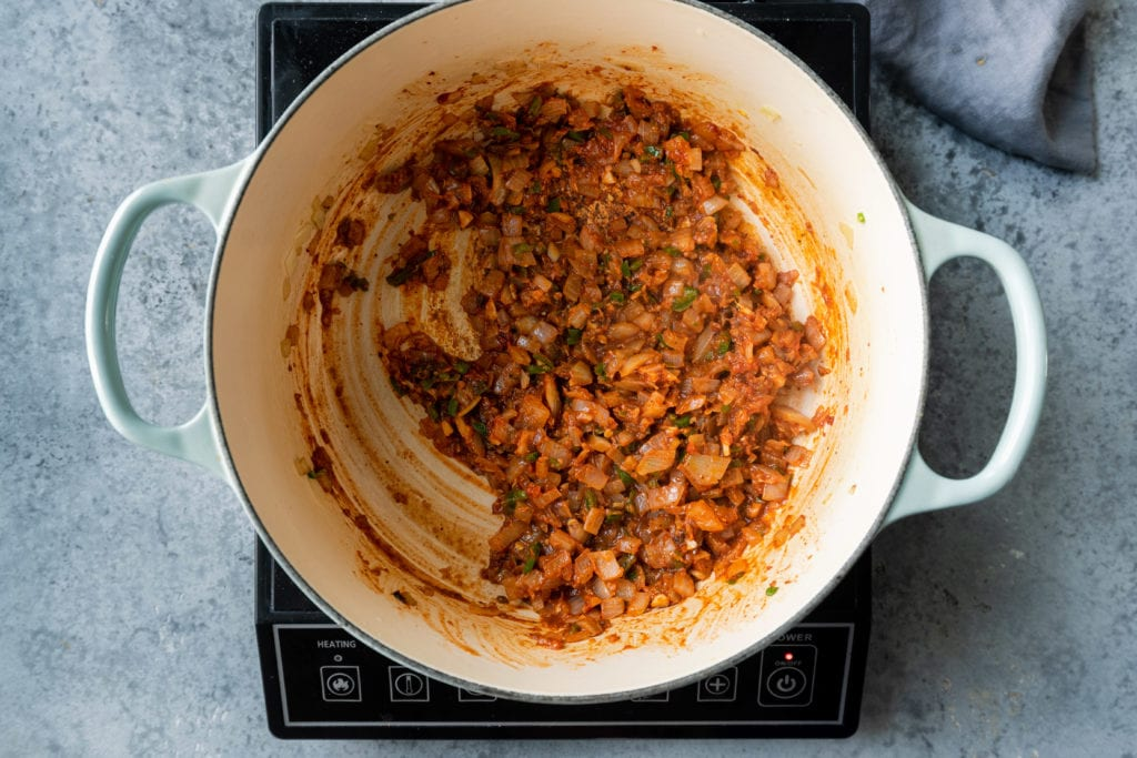 cooked onions, tomato paste and spices in Dutch oven