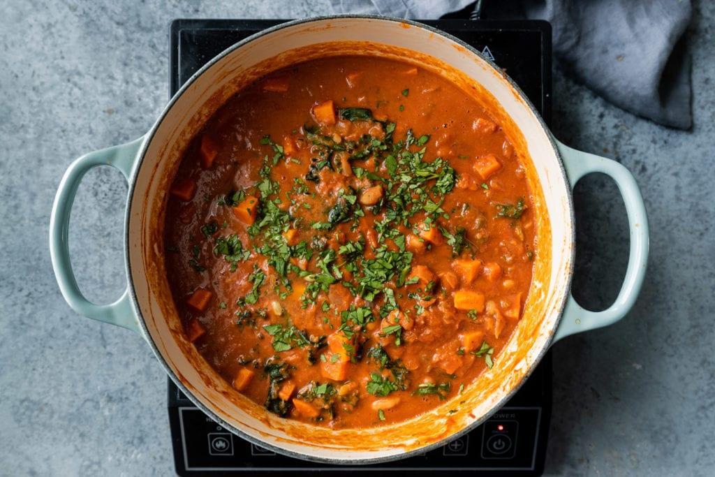 finishing gambian peanut stew with cilantro
