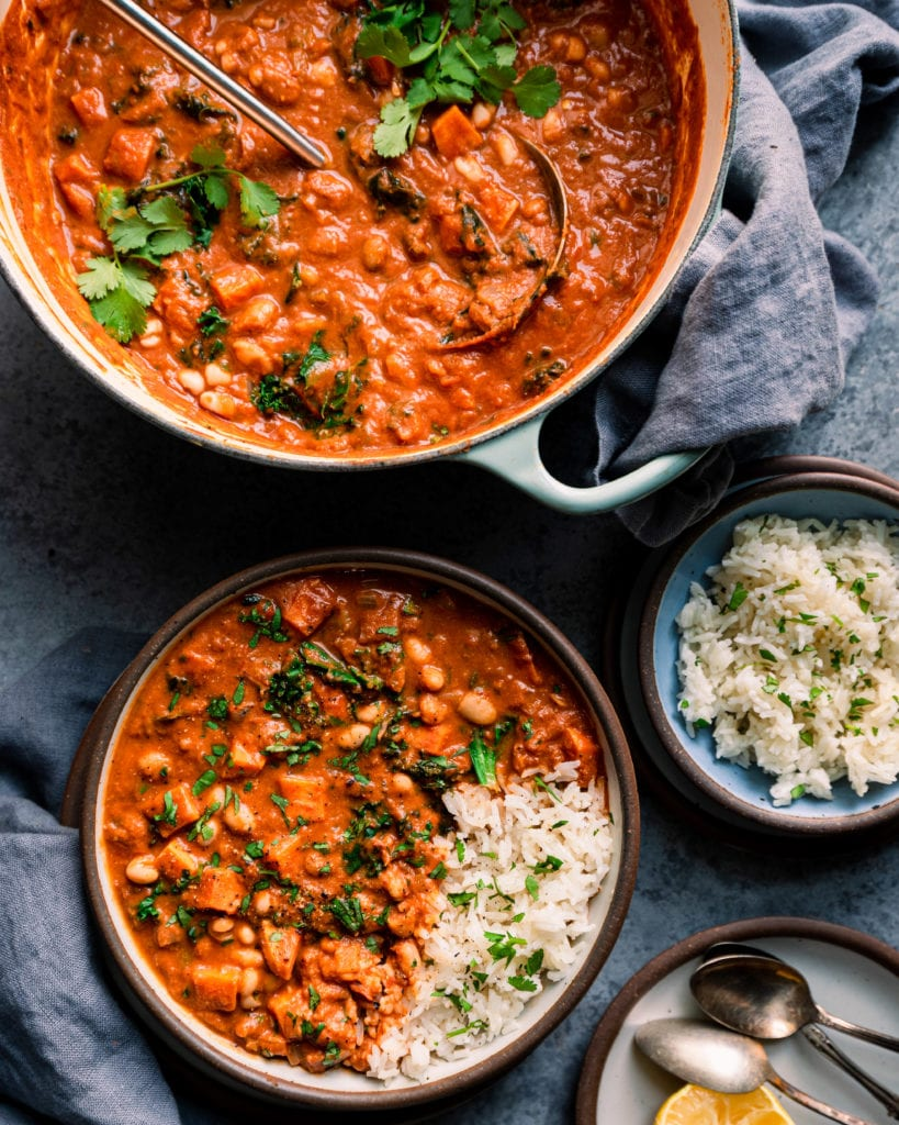 Bowl of west african peanut stew on table with dutch oven with peanut stew and bowl of rice