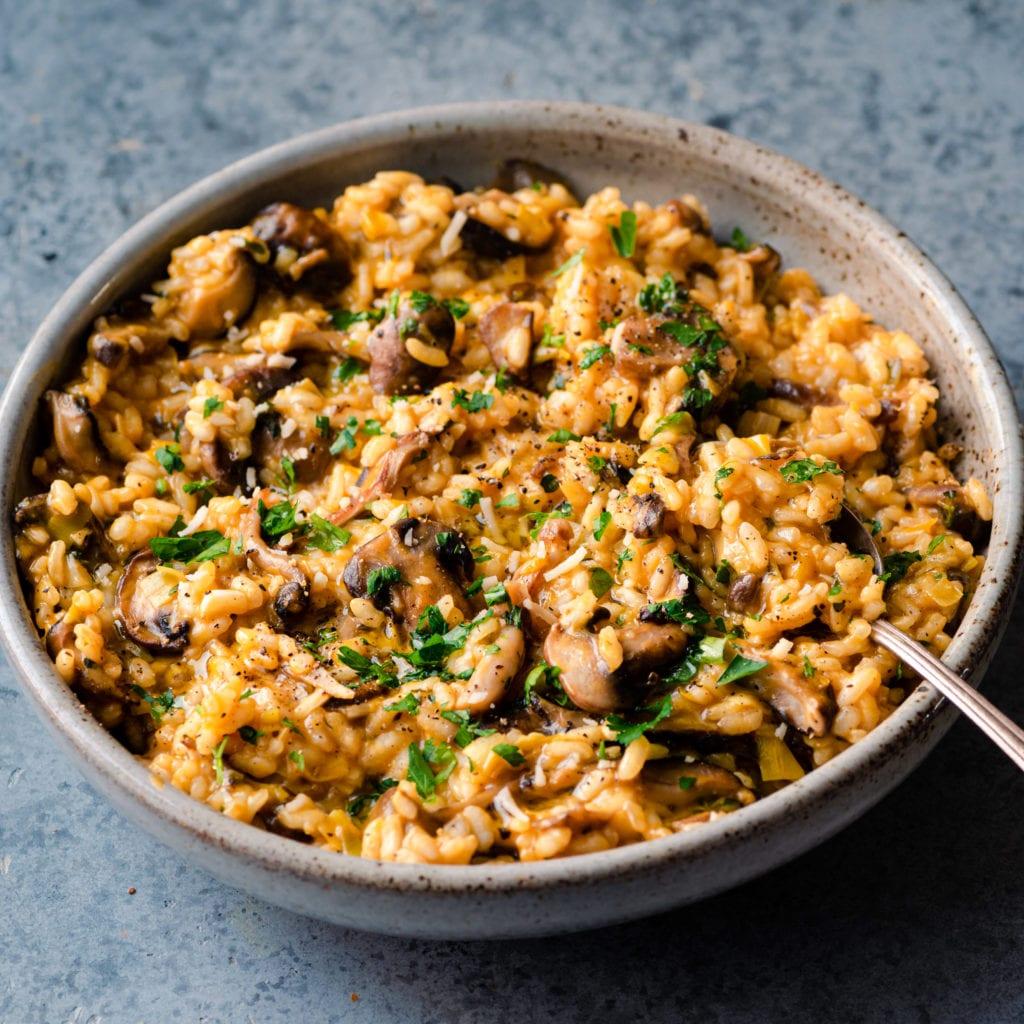 creamy mushroom risotto in ceramic bowl spoon