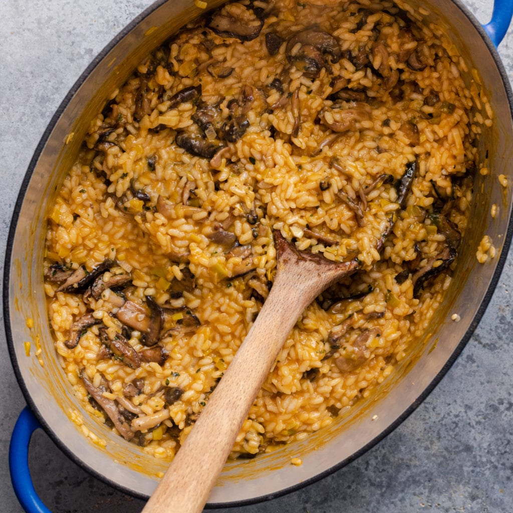 vegan mushroom risotto - mushroom risotto with serving spoon in dutch oven