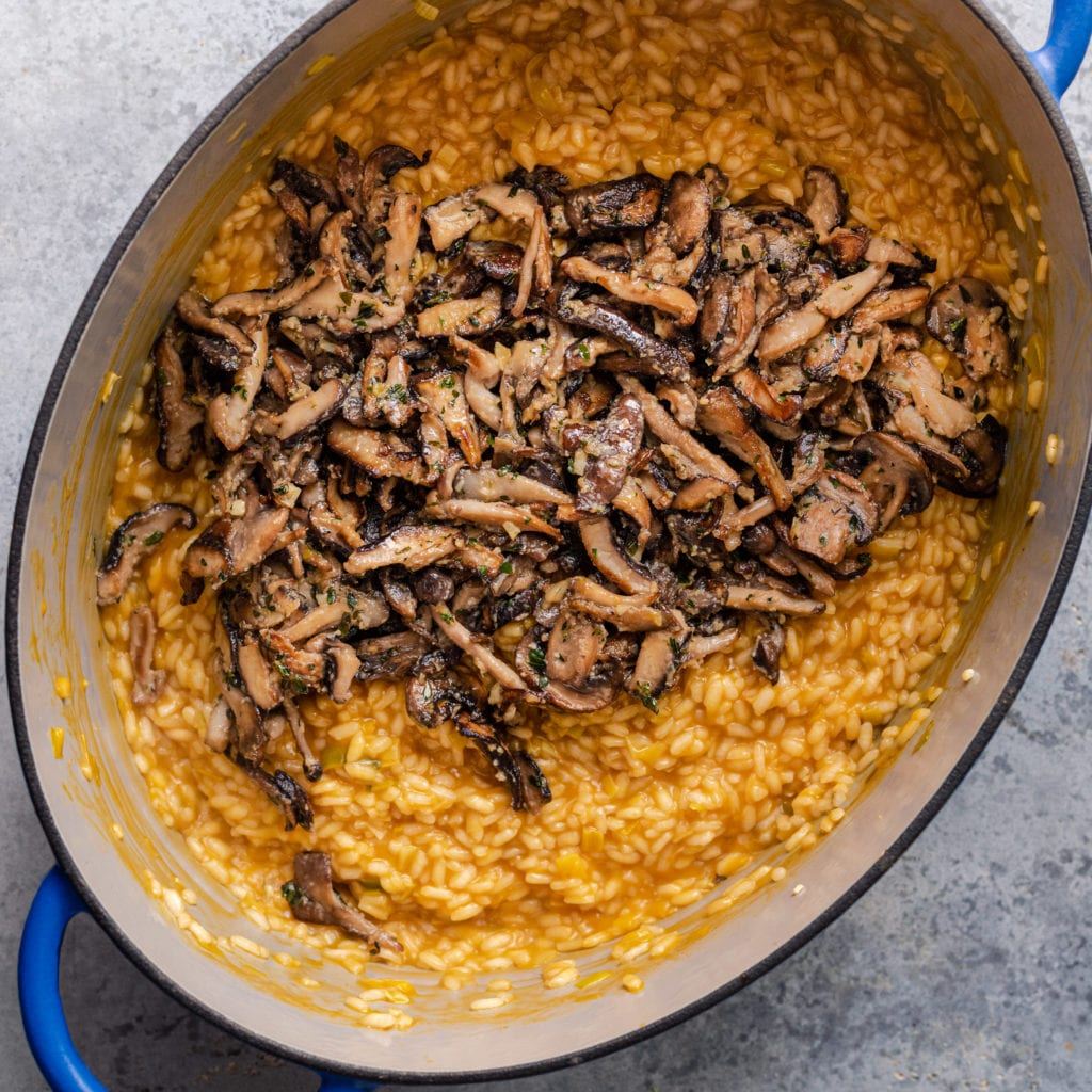 vegan mushroom risotto - a bed of mushrooms sitting on top of risotto in dutch oven