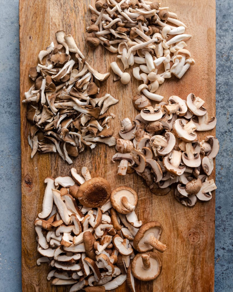 vegan mushroom risotto - a variety of sliced mushrooms on a wooden cutting board