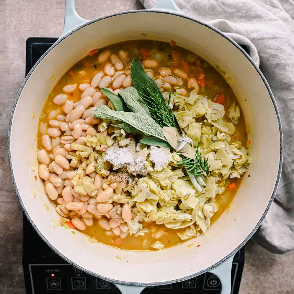 white bean soup in dutch oven with fresh herb bouquet garni on top