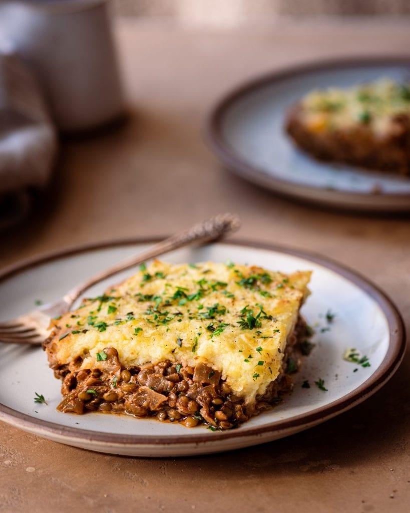 healthy vegan lentil shepherd's pie - piece of shepherds' pie on white plate