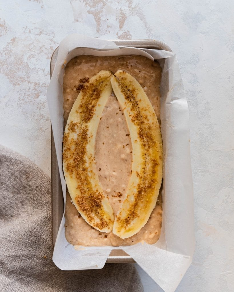 banana slices on top of banana bread batter in loaf pan