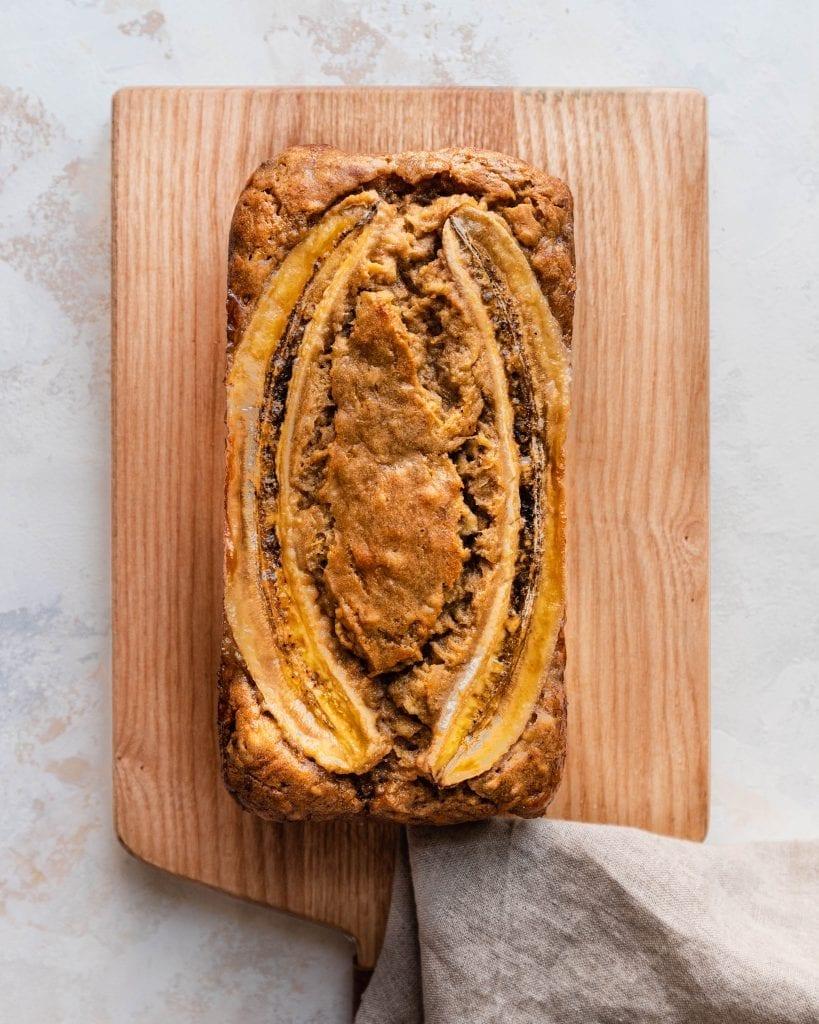 baked vegan banana bread on wooden cutting board