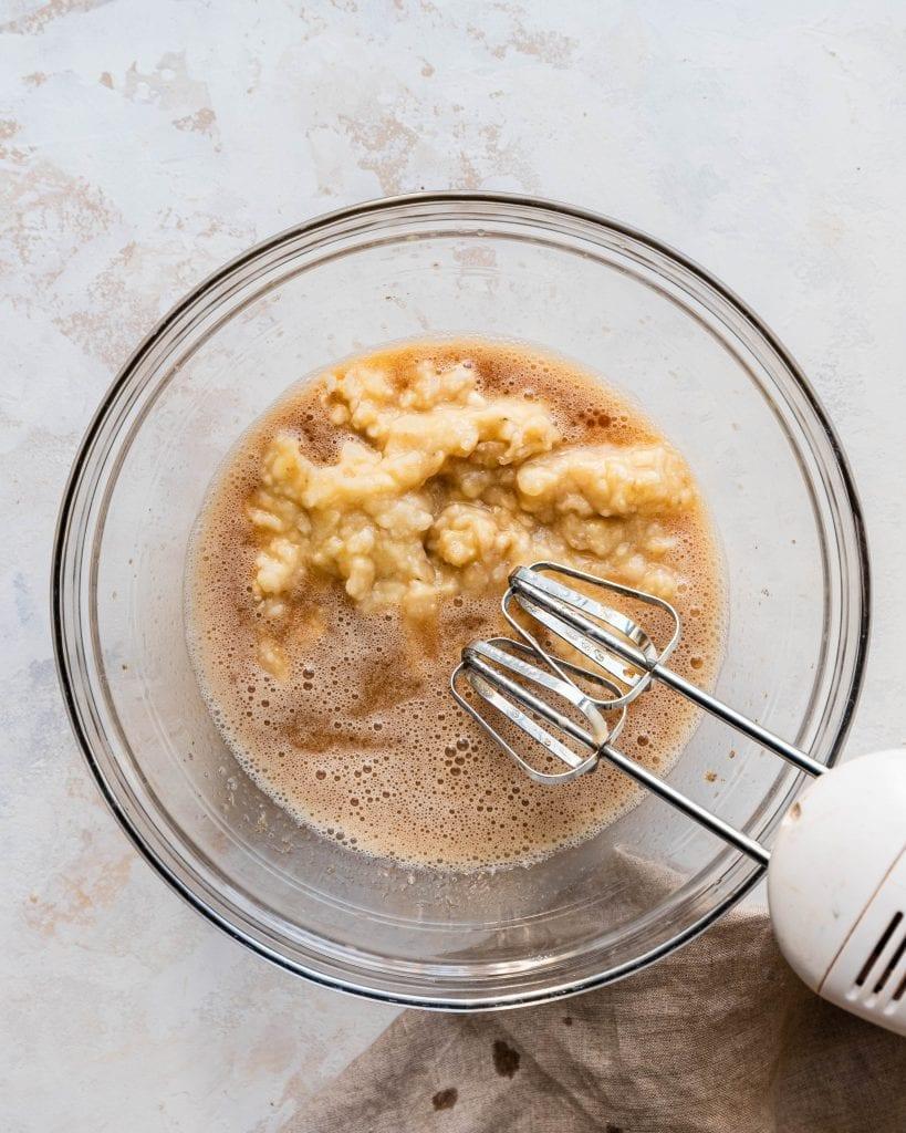 mixing mashed bananas into liquid ingredients for banana bread