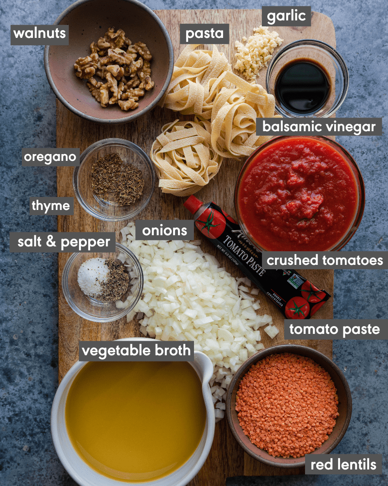ingredients for lentil bolognese on cutting board with name of ingredients