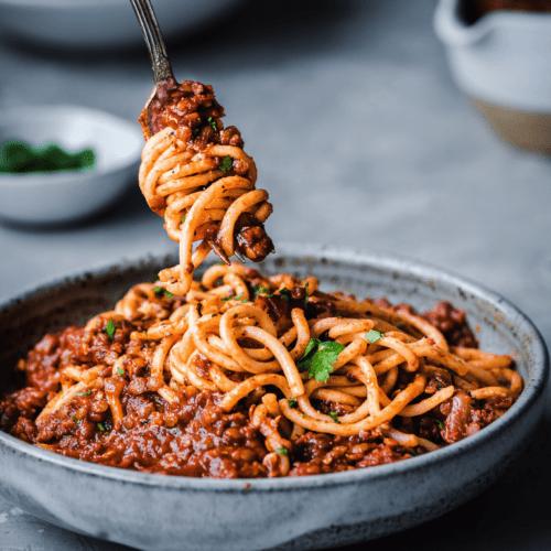 red lentil bolognese twirling on a fork