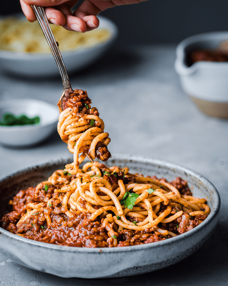 a fork twirling spaghetti in a bowl of red lentil bolognese