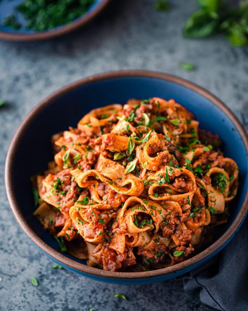 vegan lentil bolognese with wide pasta noodles in a blue bowl on a blue surface