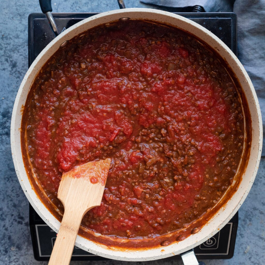 stirring crushed tomatoes into pan of lentils