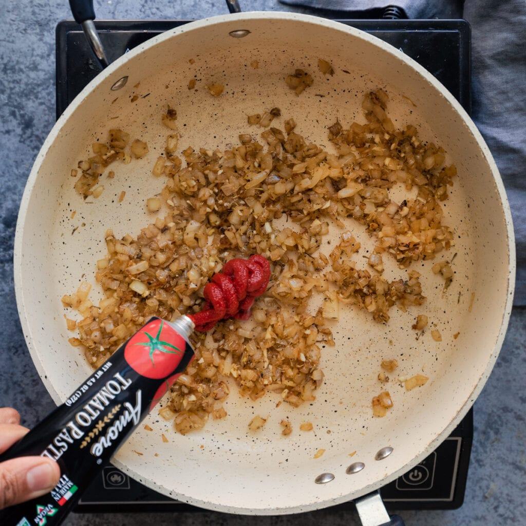 squeezing a tube of tomato paste into a saute pan of onions