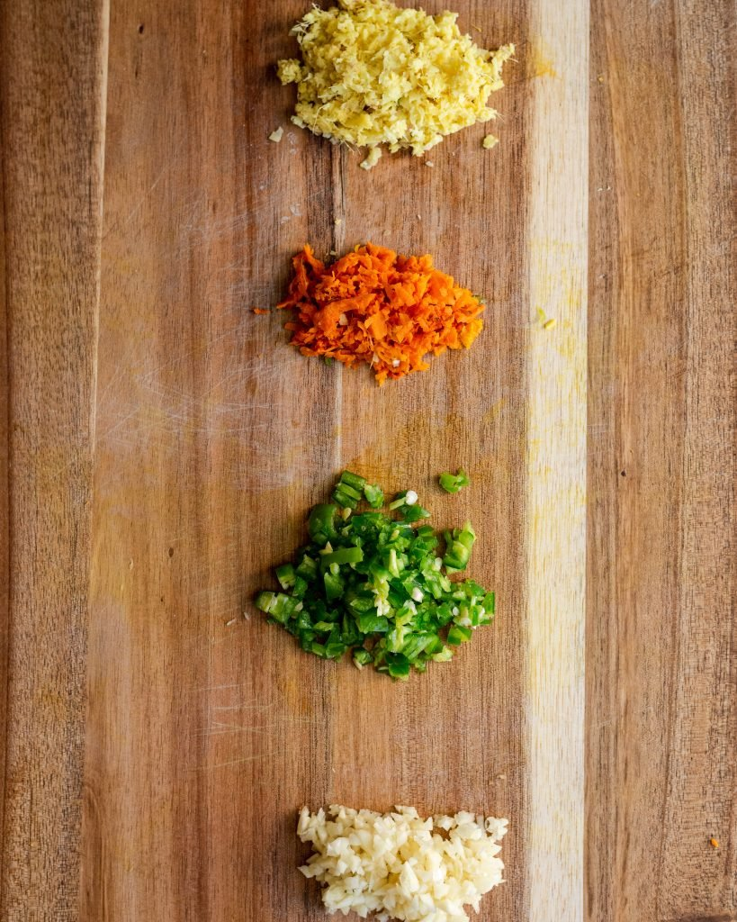 diced garlic, ginger, peppers, and turmeric on a cutting board