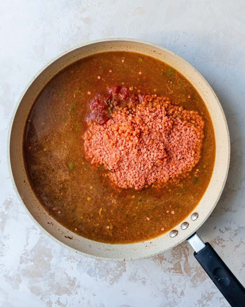 vegetable broth, red lentils, and crushed tomatoes being added to pan
