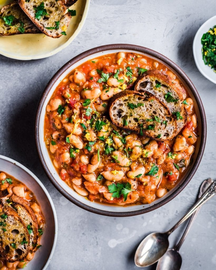 vegan instant pot white bean stew with bread slices and spoons