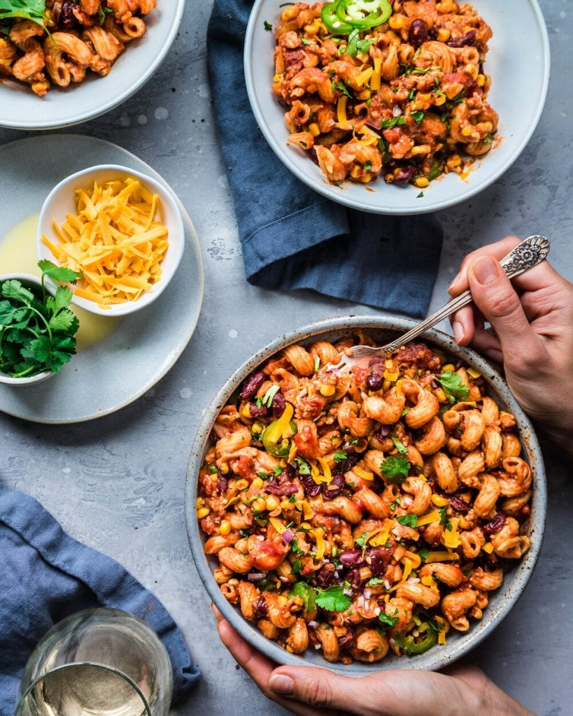 woman's hands holding bowl of chili mac