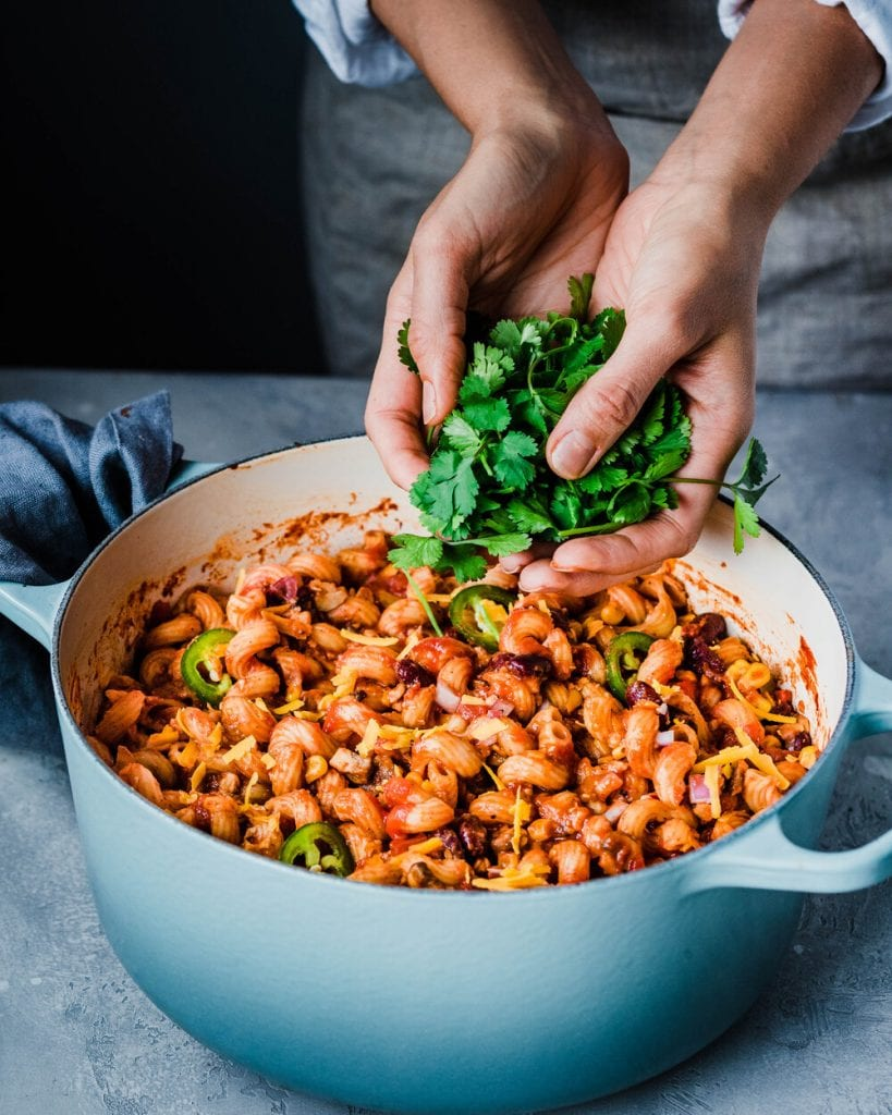 woman's hands adding cilantro to pot of vegan chili mac and cheese