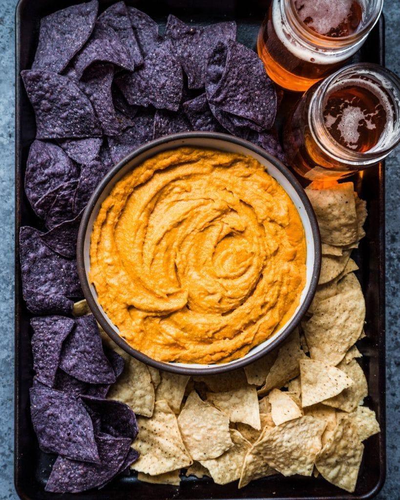 cheesy buffalo dip in a bowl surrounded by tortilla chips and beers