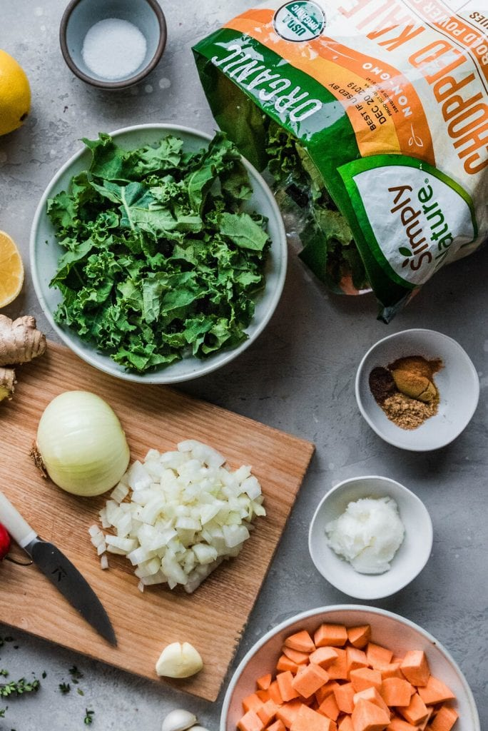 Bowl of chopped kale on table surrounded by ingredients for Gambian Peanut Stew.