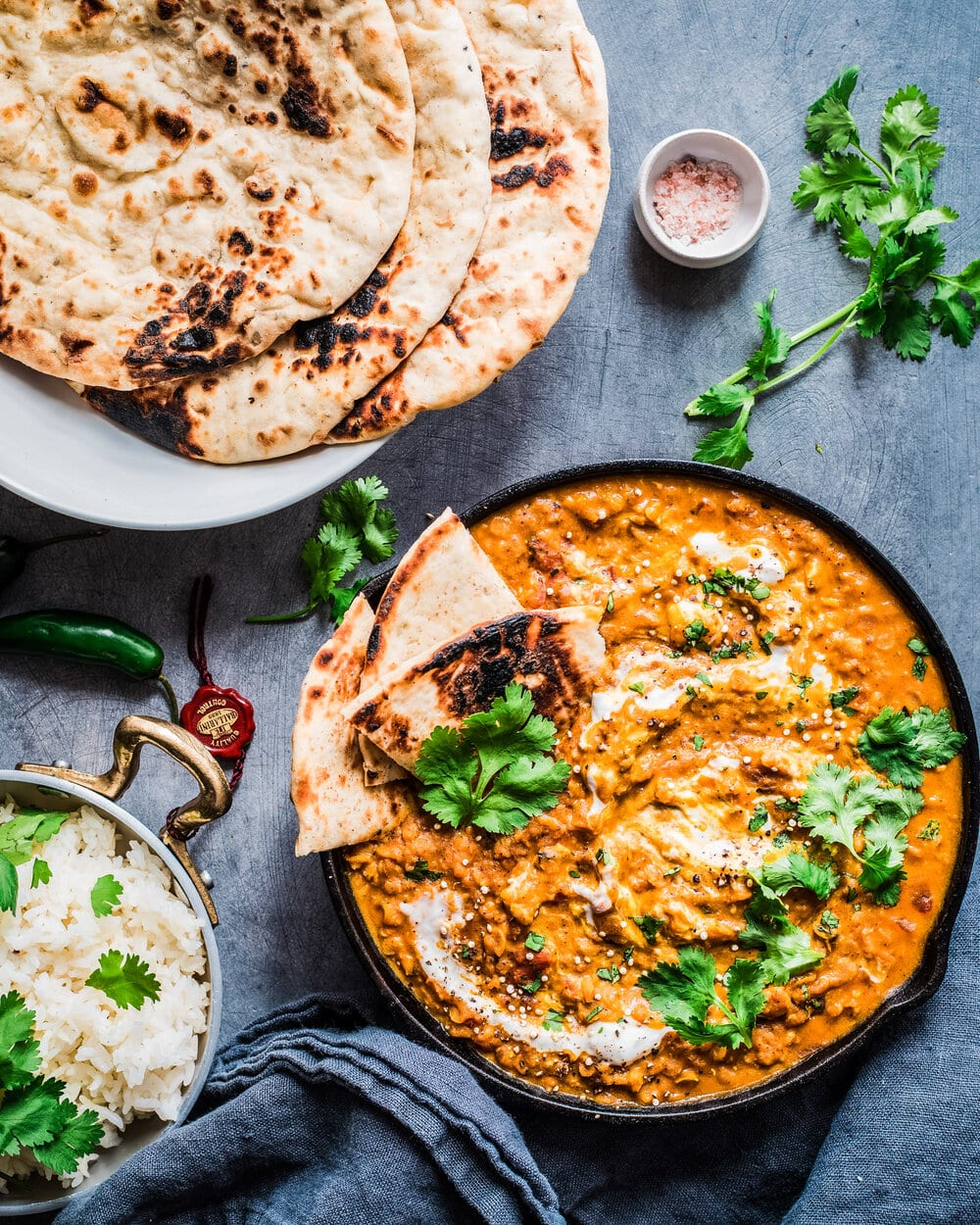 red lentil curry with naan bread, cilantro, and rice on blue table