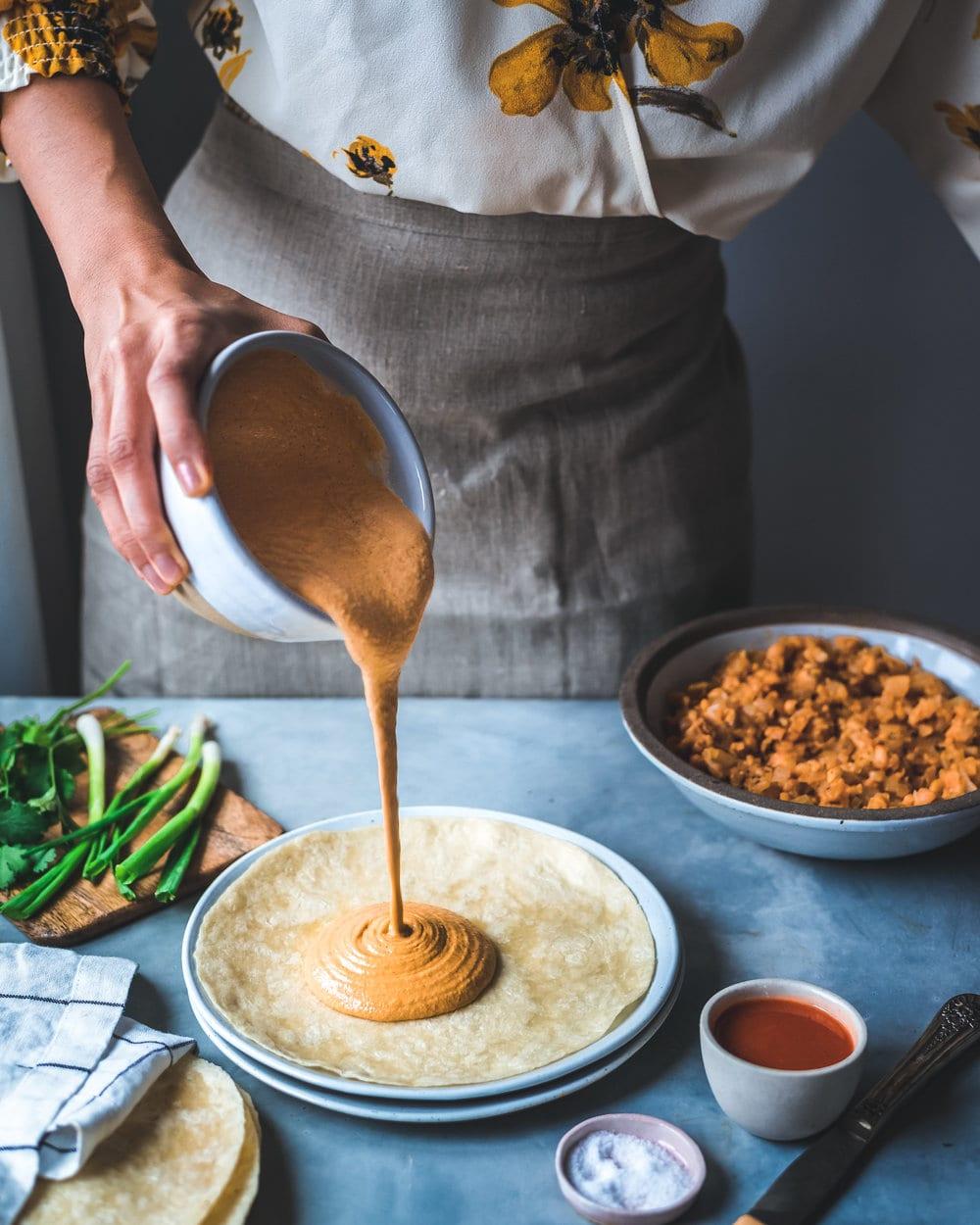 Woman pouring vegan buffalo cheese sauce onto quesadill