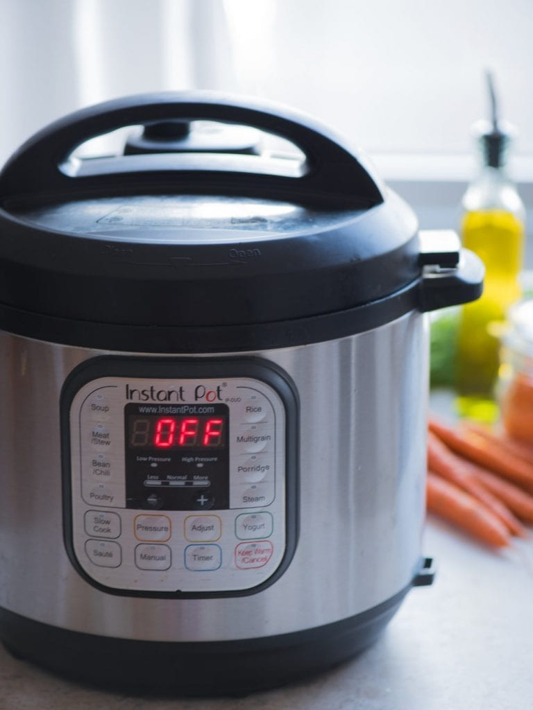 An instant pot resting on a table with carrots in the background