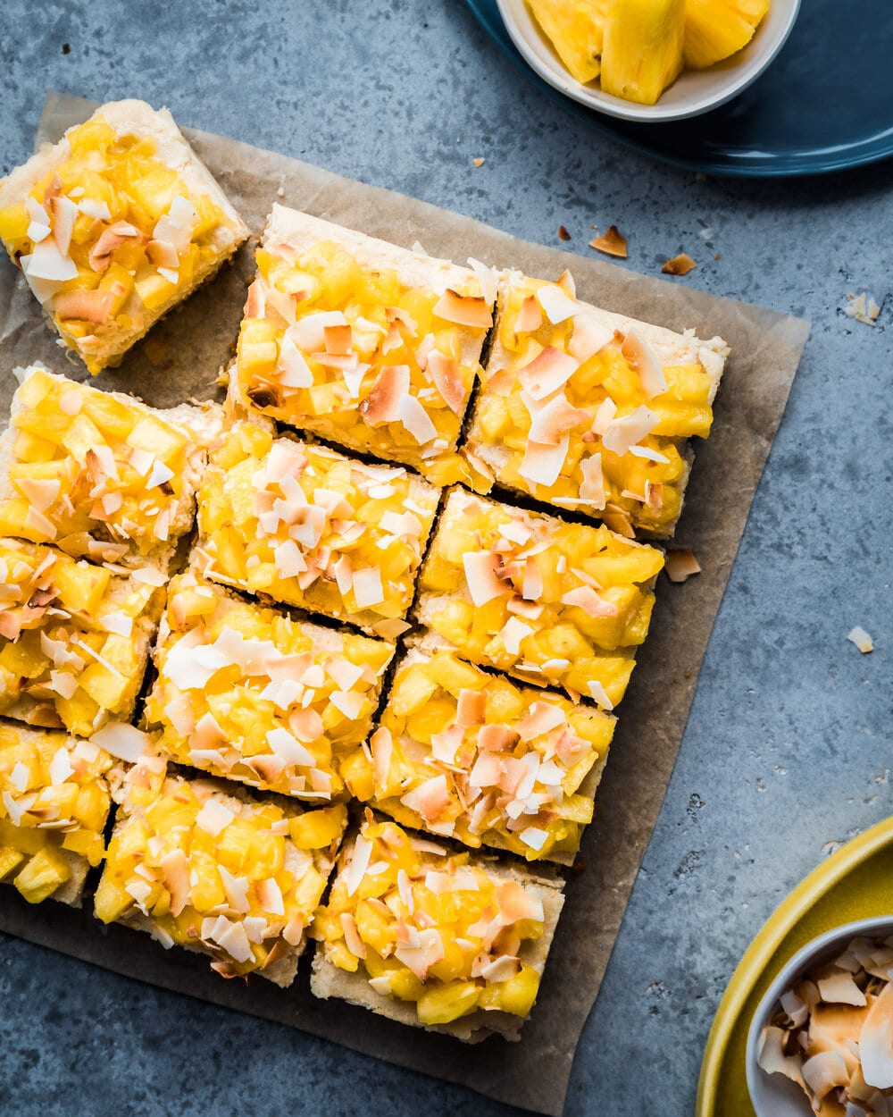 pina colada cheesecake bars on parchment paper