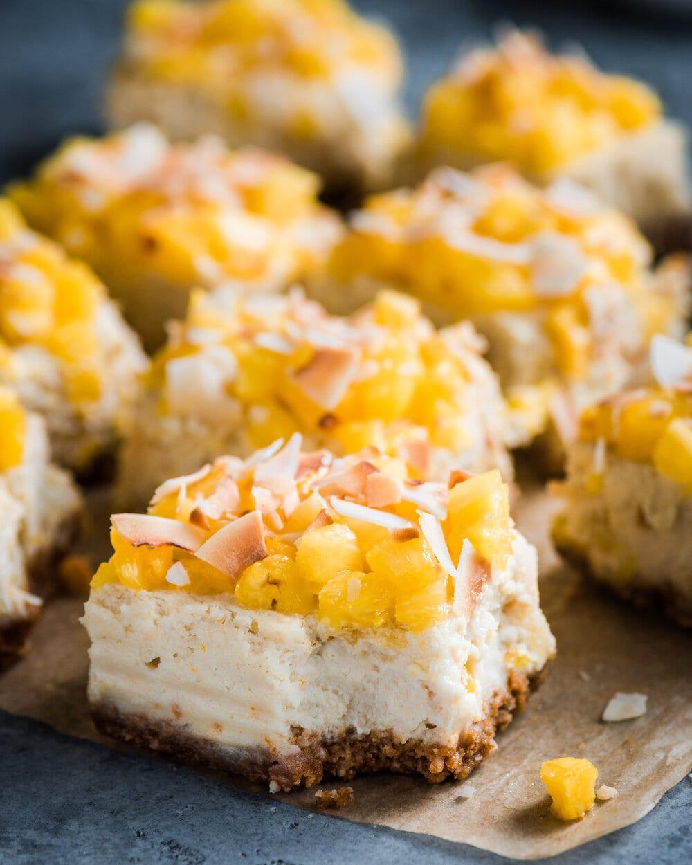 macro shot of vegan pina colada cheese cake bars on parchment paper