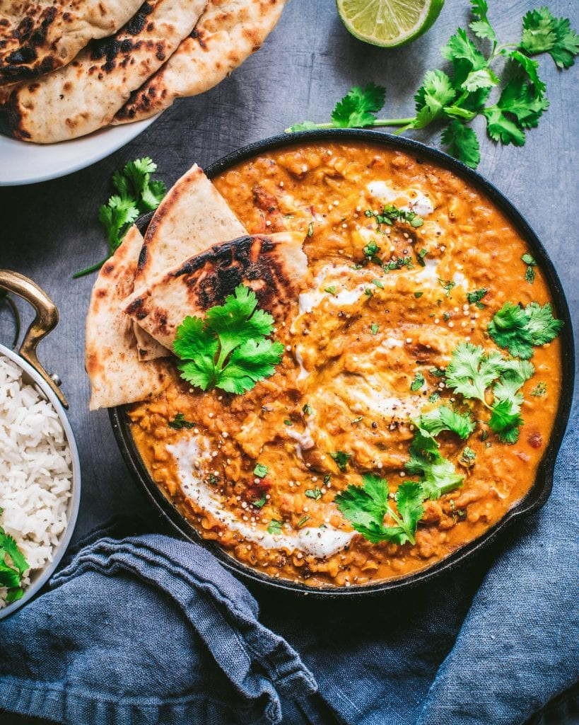 skillet with vegan red lentil curry, topped with cilantro and served with naan