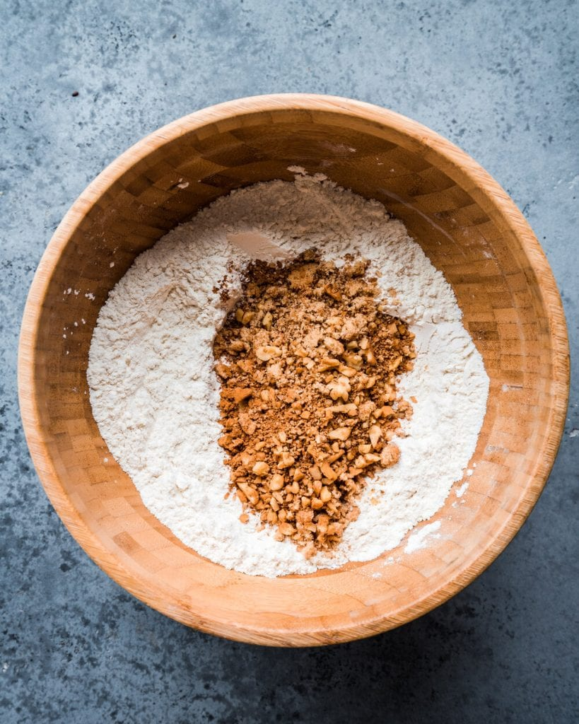 brown sugar and walnuts added to flour, baking powder, baking soda, and salt in bowl