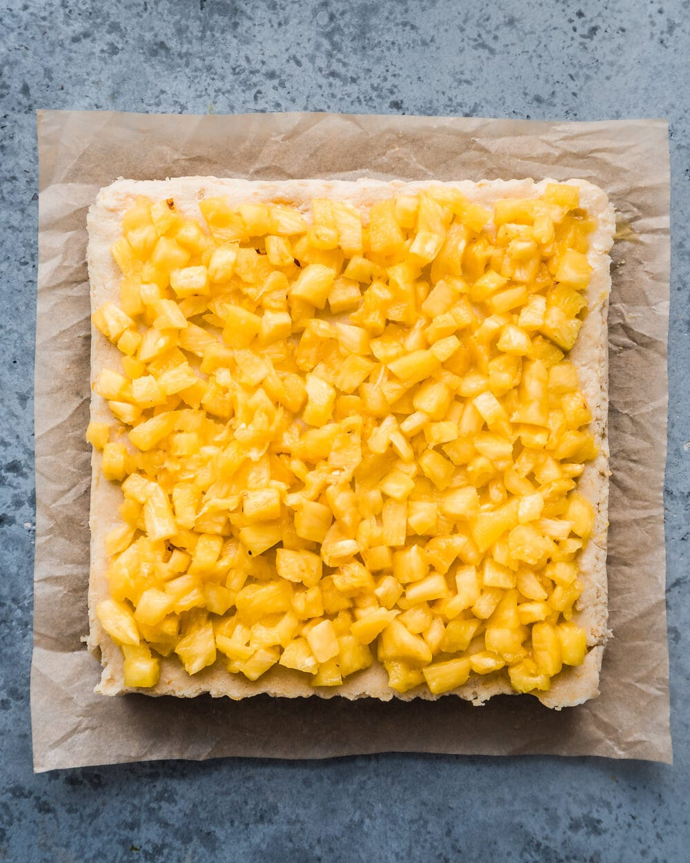 pineapple being added to cheesecake on parchment paper