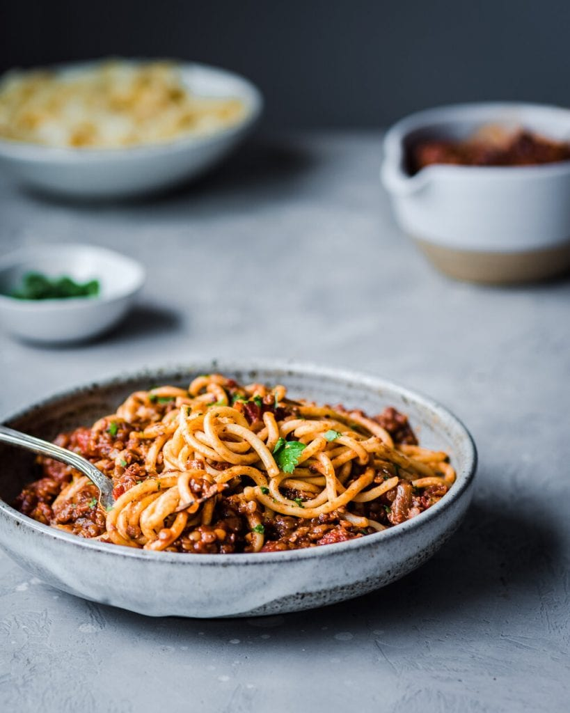 red lentil bolognese on a table, topped with parsley