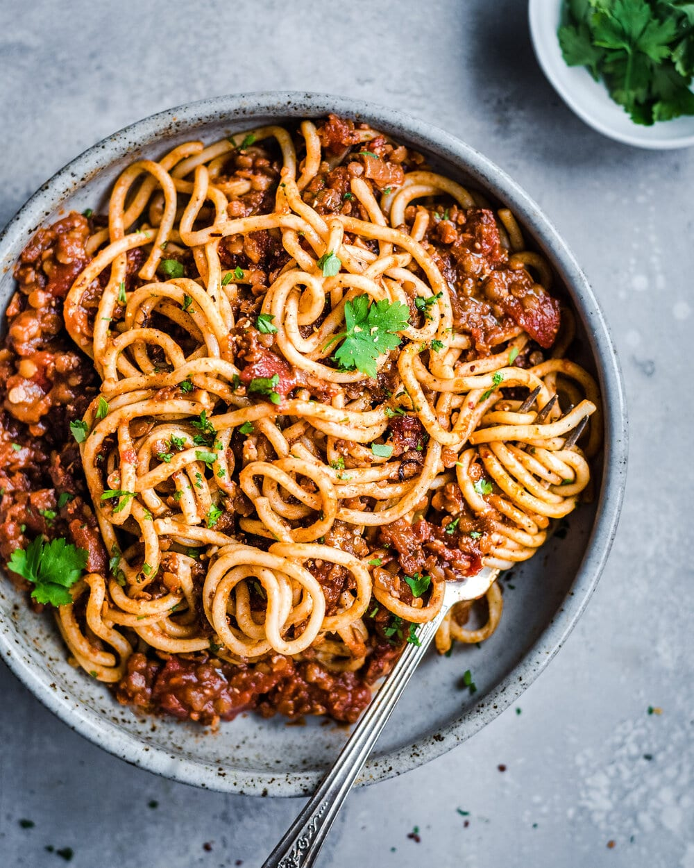overhead shot of lentil bolognese with parsley in a bowl