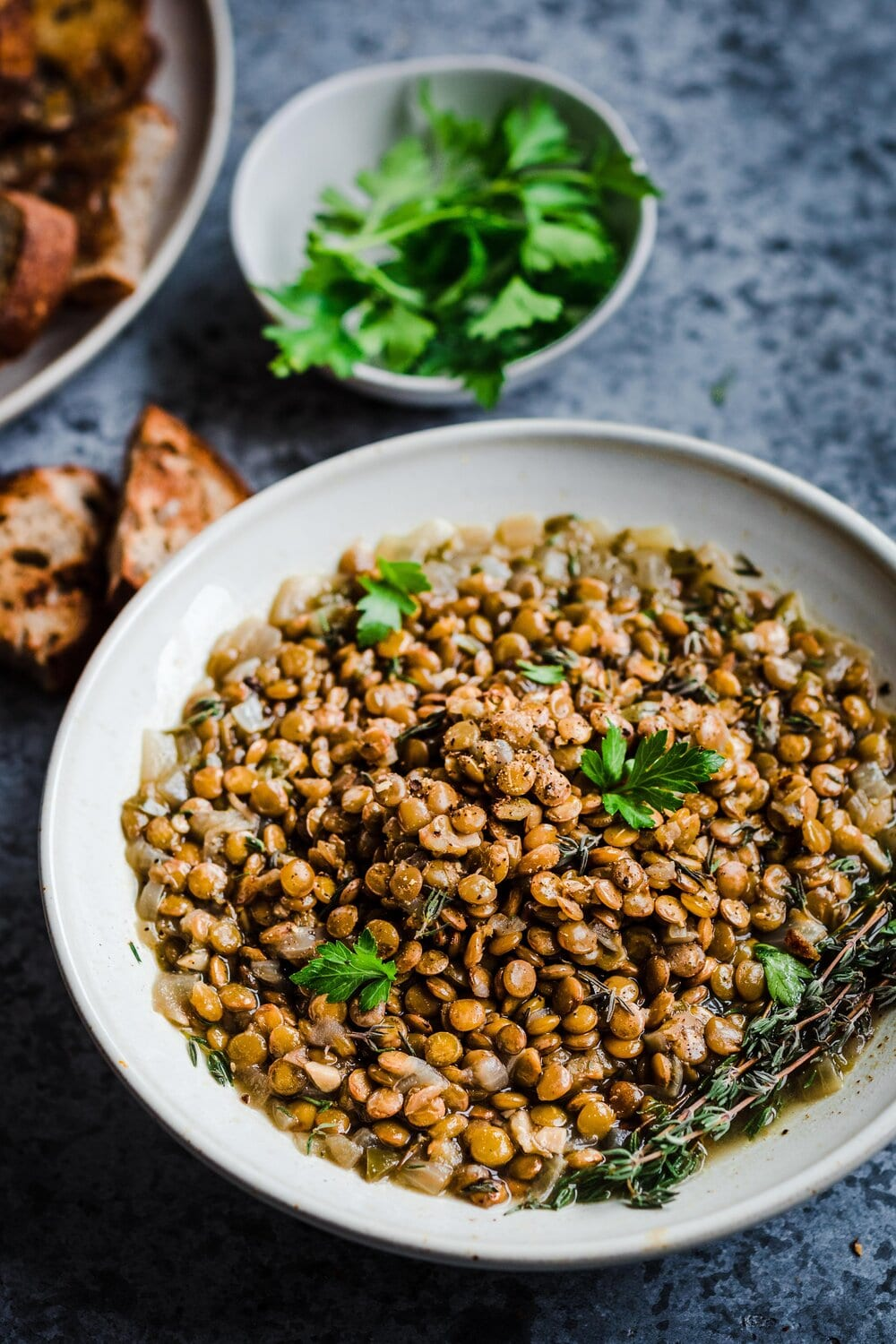 bowl of brown lentils cooked in the instant pot, flavored with parsley and thyme.