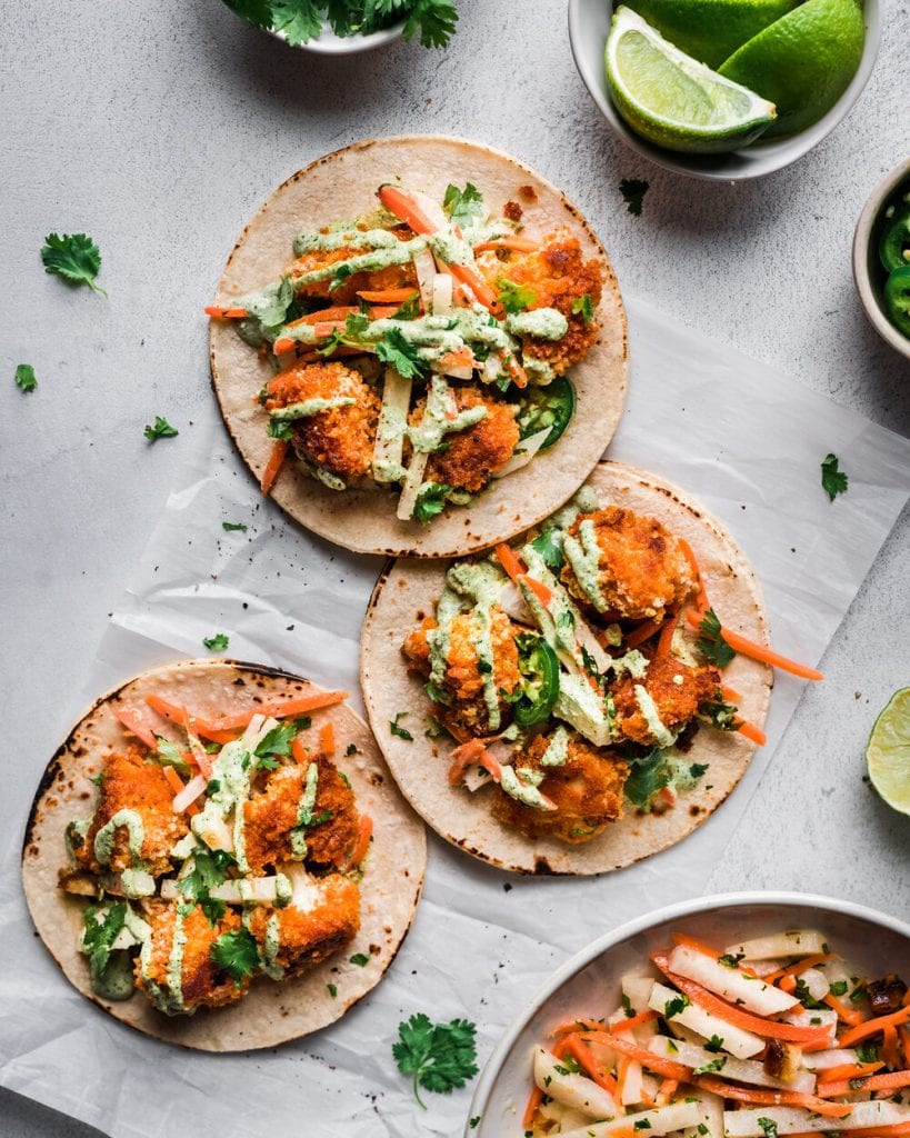 three tacos with baked crispy cauliflower on parchment paper