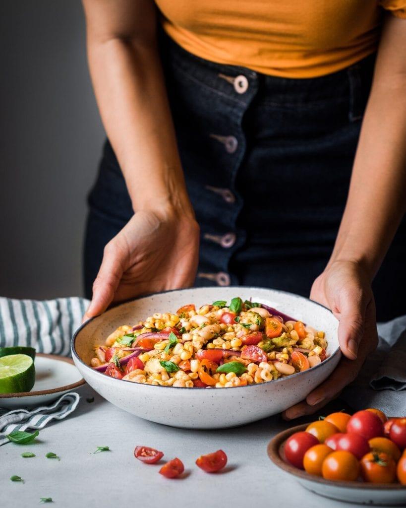 woman holding bowl of corn salad