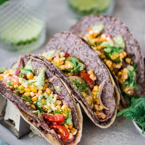 3 black bean and corn double wrapped tacos in taco holders
