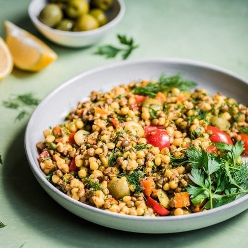 bowl of pearl couscous and lentil salad with tomatoes, parsley, and olive