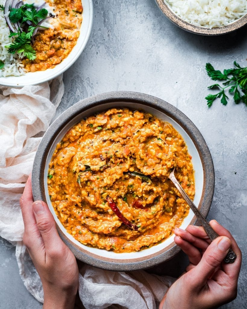 woman's hands holding bowl of dal tadka