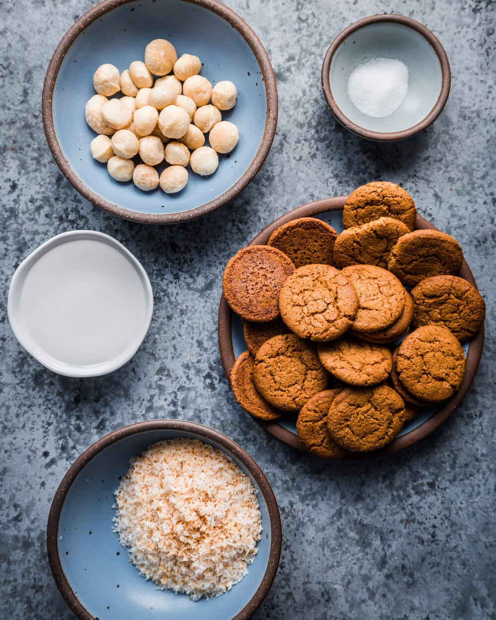 gingersnap cookies, macadiama nuts, and salt on a table