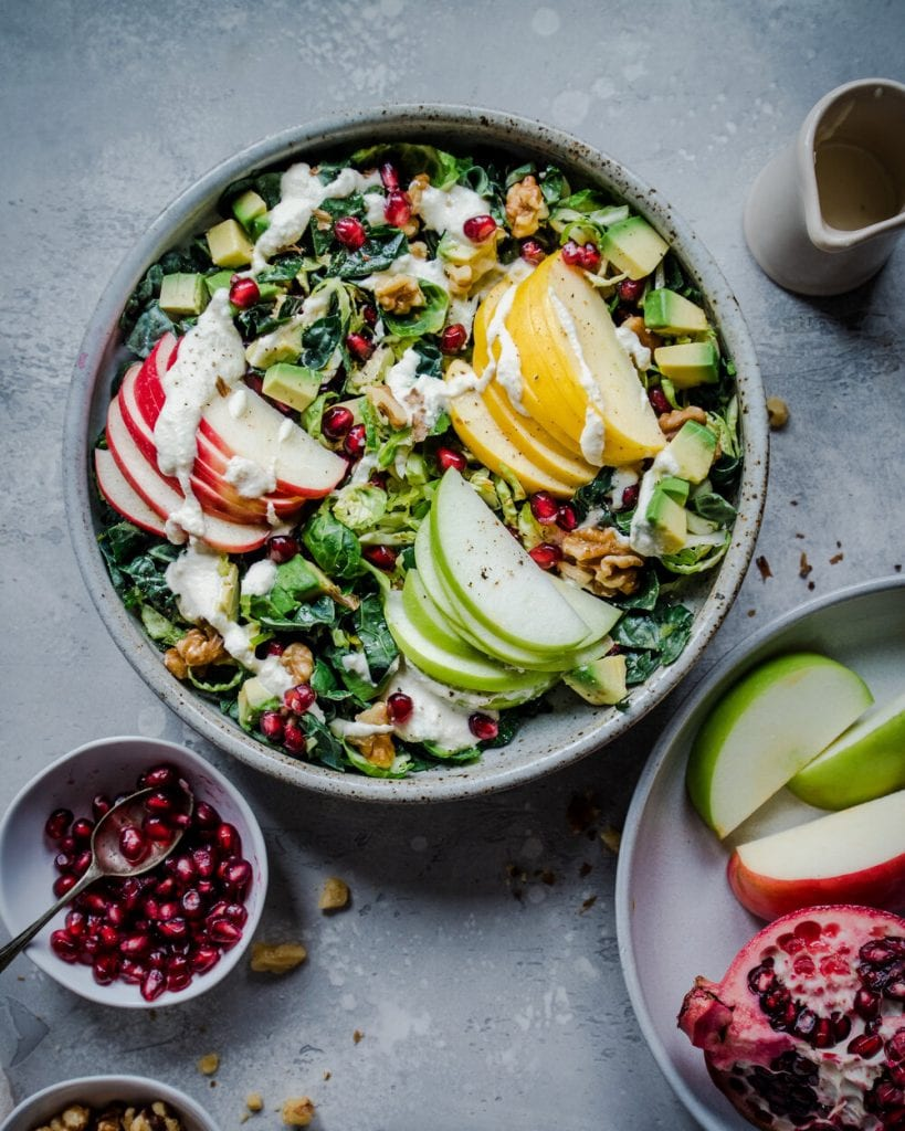 kale salad with sliced apples and pomegranates